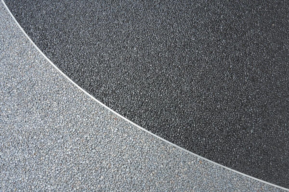 Steinteppich in verschiedenen Farben auch in einem Raum mit Edelstahlleiste zur Trennung der einzelnen Farben.